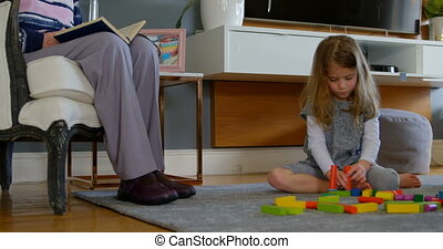 Girl playing with building blocks in living room 4k