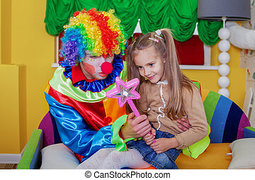 Girl playing with cheerful clown