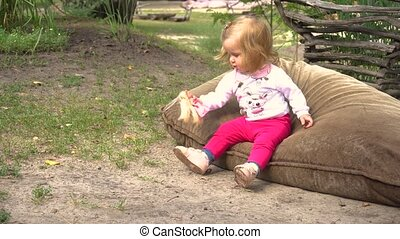 Girl playing with doll on ground - Funny little girl playing...