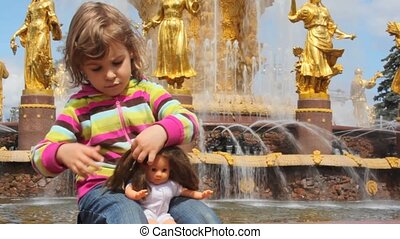 girl playing with doll with fountain friendship at All-Russia Exhibition Centre on the background