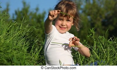 girl playing with grass making roof