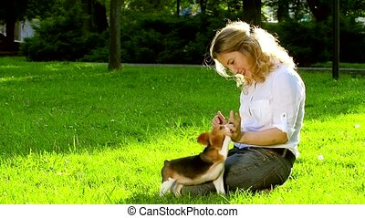 Girl playing with her beagle dog in  park. Slow motion