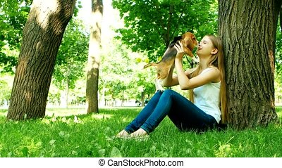 Girl playing with her beagle dog in summer park