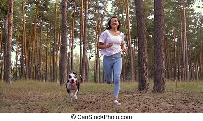 Girl playing with her dog in the forest at sunset