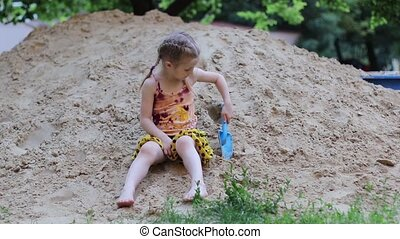 Girl playing with in a sandbox - Little girl with pigtails...