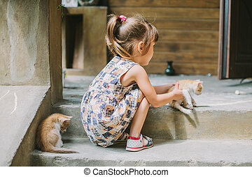 girl playing with kittens on the terrace