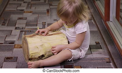 Girl playing with log