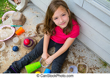 girl playing with mud in a messy soil smiling portrait...
