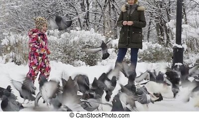 Girl playing with pigeons in winter park