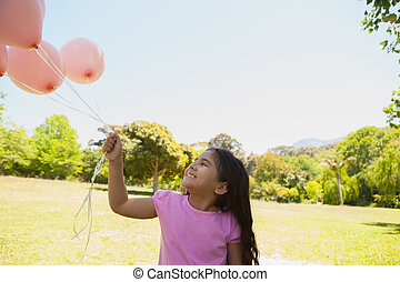 Girl playing with pink balloons at park