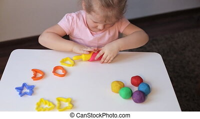 Girl playing with plasticine - Young caucasian girl playing...