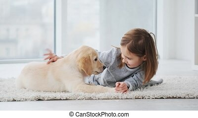 Girl playing with puppy - Cheerful girl playing with golden ...