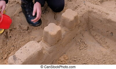 Girl playing with sand on the yard. Construction of a sand castle