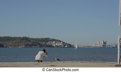 Girl playing with sea gull and looking at the river in...