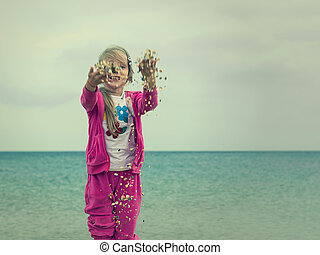Girl playing with shells on the beach in cool weather.