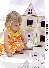 Girl playing with teapot set