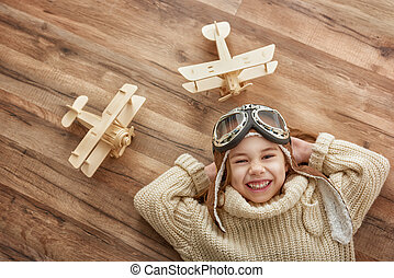 girl playing with toy airplane - happy child girl playing...
