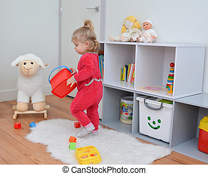 Girl playing with toys in the white children's room