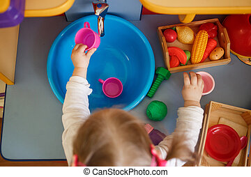 Girl playing with toys on a small toy kitchen