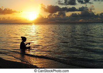 Girl playing with waves at sunset