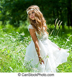 Girl playing with white dress in field.