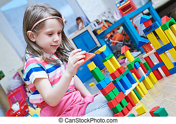 girl playing with wooden toy blocks indoors