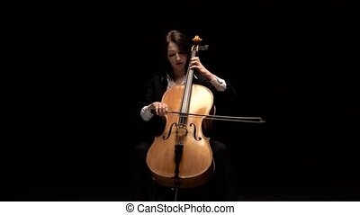 Girl plays a cello a sitting on a chair in a dark room....