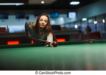 Girl plays billiards in the club.