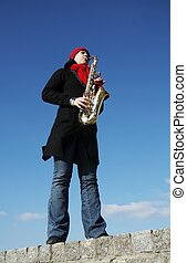Girl plays on a saxophone - Beautiful girl plays on a...