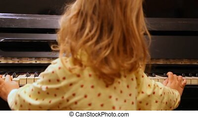 girl plays piano - little girl blonde plays piano, shooting...
