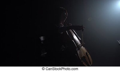 Girl plays the cello in a dark room and looks at the music stand. Silhouette. Black smoke background. Side view