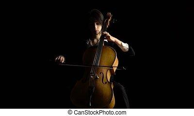 Girl plays the cello on dark studio. Black background - Girl...