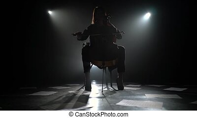 Girl plays the composition on the cello on the floor are scattered sheets with notes. Silhouette. Black smoke background