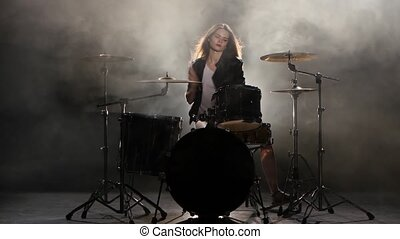 Girl plays the drum she likes to pound on pancakes. Black smoke background