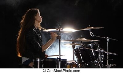 Girl plays the drum she likes to pound on pancakes. Black smoke background. Side view