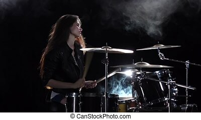 Girl plays the drum she likes to pound on pancakes. Black smoke background. Side view. Slow motion