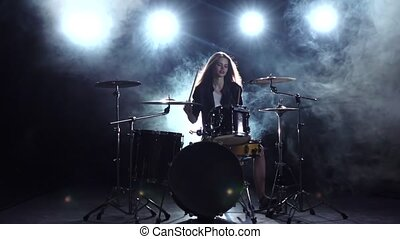 Girl plays the drum she likes to pound on pancakes. Black smoke background. Slow motion