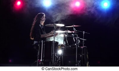 Girl plays the drums and smiles. Black smoke background. Red blue light from behind. Side view. Slow motion