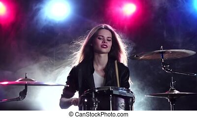Girl plays the drums and smiles. Black smoke background. Red blue light from behind. Slow motion