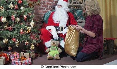Girl plays the fool with Santa near the Christmas tree
