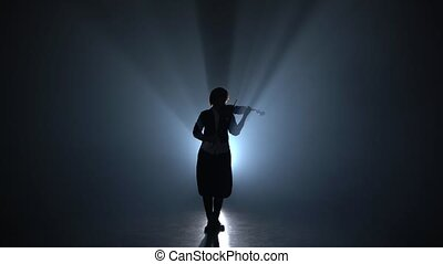 Girl plays the violin a classic composition in a dark smoky room. Silhouette. Black smoke background
