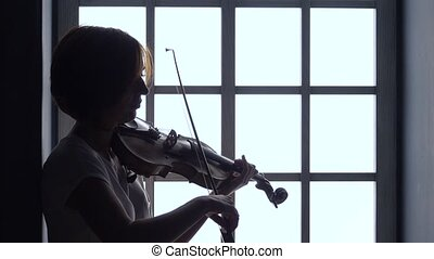 Girl plays the violin against the background of a window. Silhouette