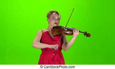 Girl plays the violin. Green screen - Girl in the red dress...