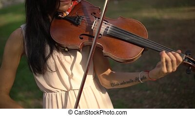 Girl plays the violin in the afternoon in the sun, close-up. High quality FullHD footage