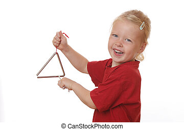 Girl plays triangle - Portrait of a young girl playing a...