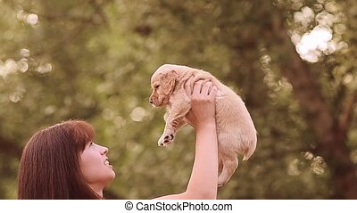 Girl plays with a little puppy