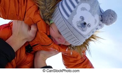 Girl plays with baby at sunny in winter time. Holding on hands. Cable-stayed bridge over the river on backgrounds