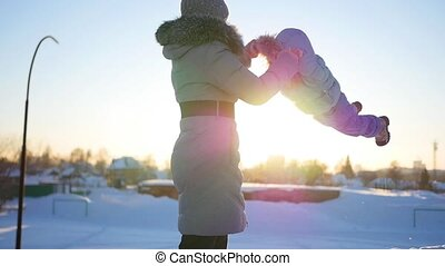 Girl plays with baby at sunset in winter time. Circling holding hands
