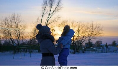girl plays with baby at sunset in winter time