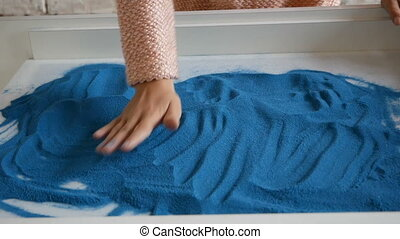 Girl plays with blue sand at the white table